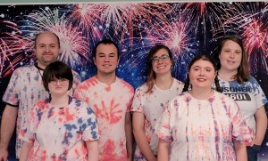 students in tie dyed shirts with firework backdrop